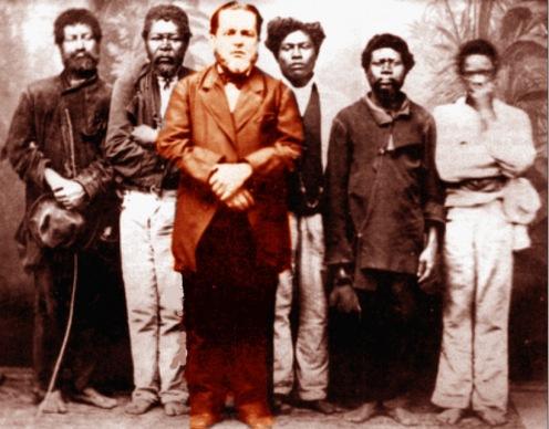 Século 19 – Um branco senhor – 'positivamente' discriminado na foto - com seus rotos e esfarrapados escravos