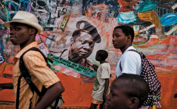 Meninos seguem um cortejo carnavalesco diante do muro com um cartaz que lembra Paul Emile de Souza, 'agudá' que foi presidente do Benin durante curto período. Outro 'agudá', o monsenhor Isidore de Souza, articulou a transição de um regime totalitário marxista, que durou 18 anos, à democracia no começo dos anos 1990. Eles e mais uma penca de ilustres membros da família 'Souza' são descendente diretos de Xaxá de Ajudá.
